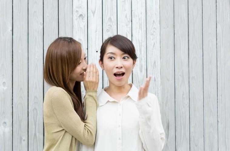 内緒話をする若い女性
