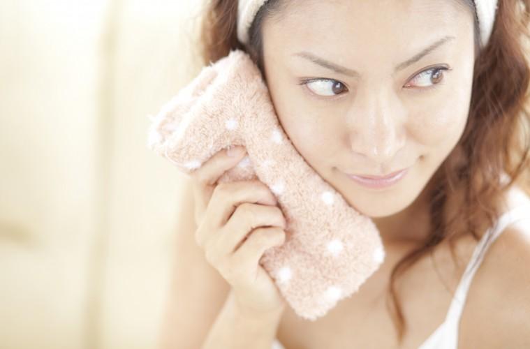 タオルで汗を拭く若い女性