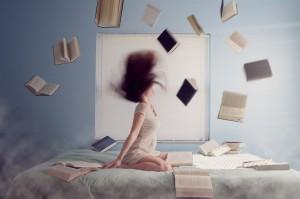 髪を振り上げる女性と散乱する本