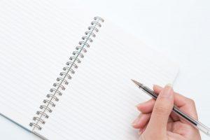 ノートとペンを持った手