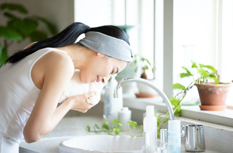 洗顔後にタオルで顔を拭く女性